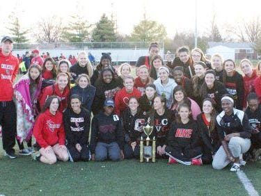 Churchill's girls track-and-field team pose with their first-place trophy.