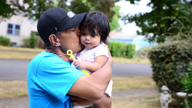 Joaquin Lizama holds his 1-year-old daughter, Destiny. Lizama and his family of 10 were displaced after a fire destroyed their NE Salem home earlier this month.