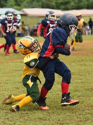 Shane O'Mallan (17) of the Guam Scuba Company Giants drags a Packers defender during his Triple J Ford GNYFF Youth Football League game at Hal Shiroma Field in Dededo on Oct. 4.Frank San Nicolas/Pacific Daily News/fsannicola@guampdn.com
