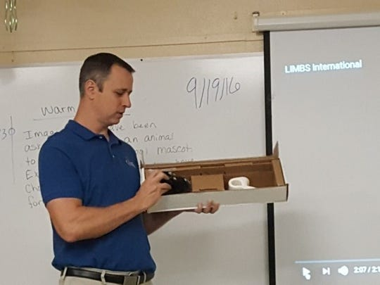 Trevor Bergman, executive director of Limbs International, instructs students of Zia Middle School's National Junior Honor Society about how a prosthetic limb is made during a presentation in September 2016.