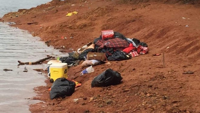 U.S. Forest Service personnel spent much of Monday cleaning up trash left behind after college students partied on Slaughterhouse Island in Lake Shasta over the weekend.