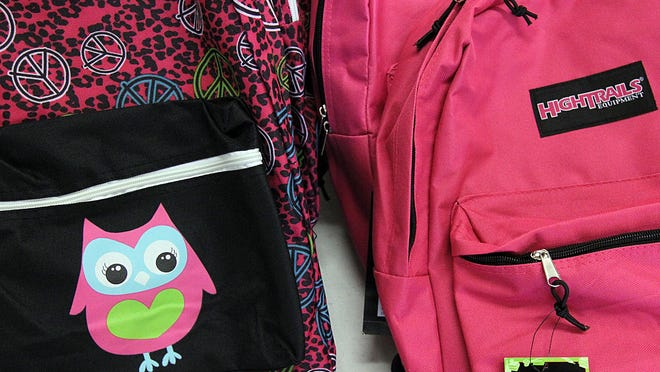 Backpacks are positioned on a table during the annual Tools for School school supply giveaway at the Delaware County Fairgrounds in August 2013.