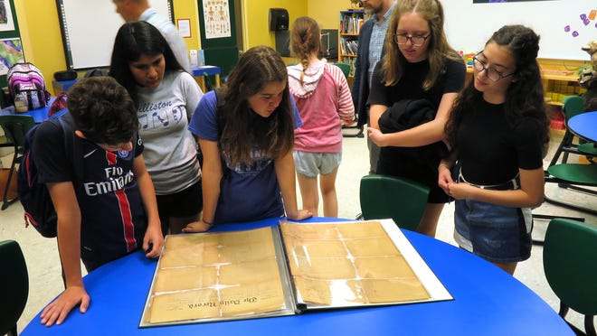 Middle school students from Williston Middle School and Friends School of Wilmington looking over a copy of The Daily Record at the Cape Fear Museum in 2017. It's part of area teachers' efforts to help students learn about the Wilmington 1898 coup, which resulted in the paper's building being burned when a mob of white supremacists overthrew the progressively diverse local government.