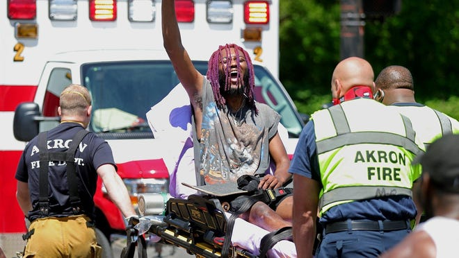 """Daquane Stephens shouts """"black lives matter"""" as he is hauled away on a stretcher after being hit by a motorist while protesting at the intersection of South Arlington and Johnston streets on Sunday."""