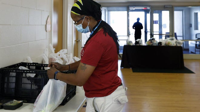 South Side Roots chef Ashena Clinkscales prepares takeout bags for folks picking up lunch last week. The cafe has been closed since March 17 but is distributing several hundred prepackaged meals per day as part of its affiliation with the Mid-Ohio Food Collective.
