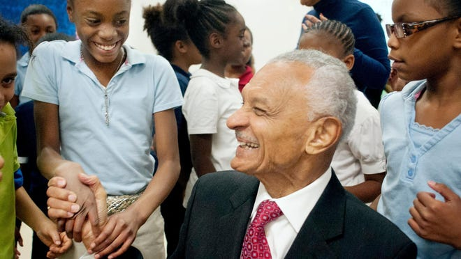 Fourth grader Breasia Smith, left, shakes hands with Rev. C.T. Vivian at Glen Oak Community School after Vivian finished speaking to the class in this November 2013 file photo. Vivian, a former Peoria resident and a civil rights activist, died Friday at age 95.