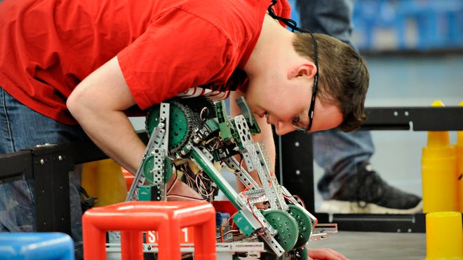 """St. Cloud State University """"Husky Team 1"""" member Logan Mildenberger makes a last adjustment of a robot before a qualifying round in the VEX U regional qualifier competition in the fieldhouse at St. Cloud State University on Saturday."""