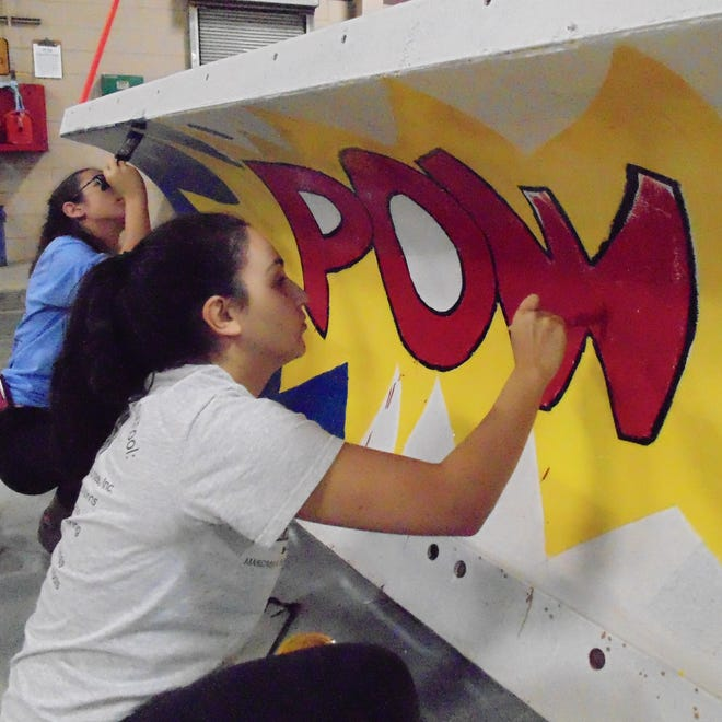 "Eat your heart out Batman. Allie Clarkson, a North junior, brings back a bit of super hero with her ""Pow"" design. Rachel Gerth, a North senior, helps."