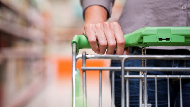 Young woman with pushcart in supermarket