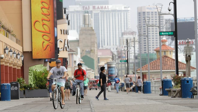 Casinos give backdrop as men ride bicycles on the boardwalk in Atlantic City.