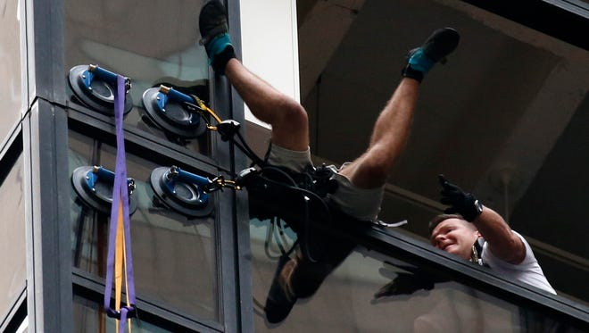 New York City police officers grab a man who climbed the Trump Tower on Aug. 10, 2016.