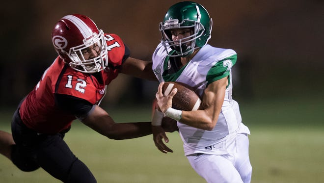 Greenville's Terrence Gist (12) runs down Easley's Bailey Catoe (2) during the Red Raiders' 32-0 win over the Green Wave Friday at Sirrine Stadium.