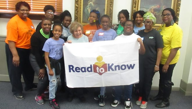 Read to Know founder, Lolly Burgin (front row, second from left), with volunteers at the organization's annual book giveaway, held at the main branch of the Paterson Public Library.
