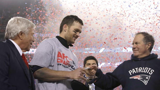 New England Patriots head coach Bill Belichick, right, passes the AFC Championship trophyto quarterback Tom Brady after winning the AFC championship NFL football game against the Pittsburgh Steelers, Sunday, Jan. 22, 2017, in Foxborough, Mass. At left is team owner Robert Kraft. The Patriots defeated the the Steelers 36-17 to advance to the Super Bowl.(AP Photo/Charles Krupa)