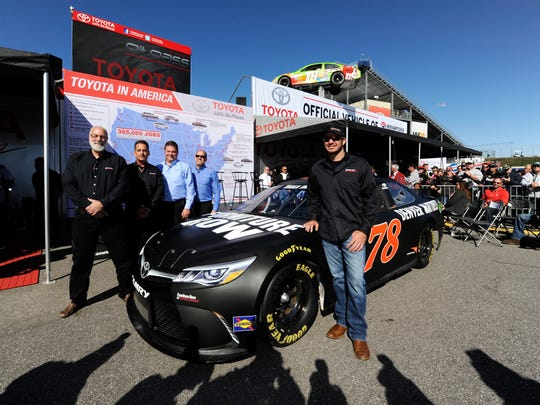 Martin Truex Jr. poses after signed a one-year contract extension with Furniture Row Racing before last weekend's  NASCAR Sprint Cup Series SYLVANIA 300 at New Hampshire Motor Speedway.