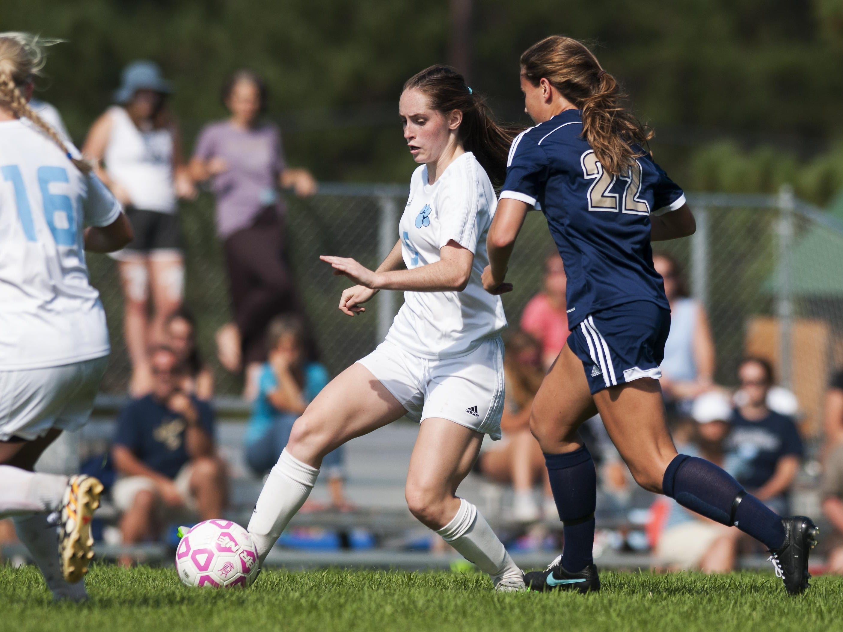 MMU's Molly Finn (5) runs past Essex's Jessica Poratti (22) with the ball during the girls soccer game between the Essex Hornets and the Mount Mansfield Cougars on Saturday in Jericho.