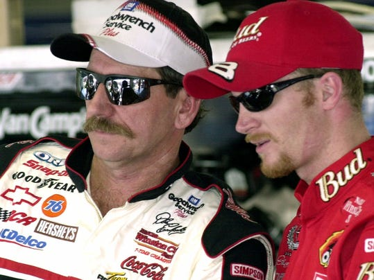 FILE - In this Friday, Feb. 9, 2001 file photo, NASCAR drivers Dale Earnhardt, left, and his son Dale Jr., stand together during a break in practice at the Daytona International Speedway in Daytona Beach, Fla. Dale Earnhardt Jr. worked with Goodyear to make a new commercial that honors his late father and shows the family history with the tire maker. The ad will debut in the season-opening Daytona 500, Sunday, feb. 18, 2018. Earnhardt is proud of the piece because of the way it celebrates his father. (AP Photo/Paul Kizzle, File)