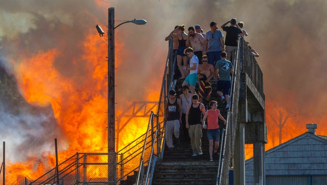 Onlookers watch the Civic Stadium burn in Eugene, Ore. on Monday, June 29, 2015.
