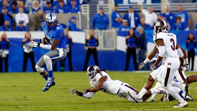 Kentucky's Demarco Robinson (#2) leaps out of the reach of Mississippi State's Jamerson Love (#5) to keep the play alive. 