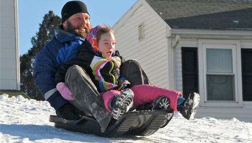 Joe Fabiani, of Cressona, Pa., and his daughter Chloe Fabiani, 7, of Schuylkill Haven, Pa., sled ride down a hill at the Schuylkill Haven, Pa. high school on Saturday, Jan. 31, 2015. (AP Photo/The Republican-Herald, Andy Matsko)