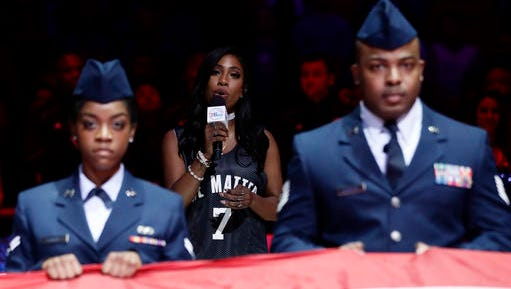 Sevyn Streeter, center, sings the national anthem before an NBA basketball game between the Philadelphia 76ers and the Los Angeles Lakers, Friday, Dec. 16, 2016, in Philadelphia.
