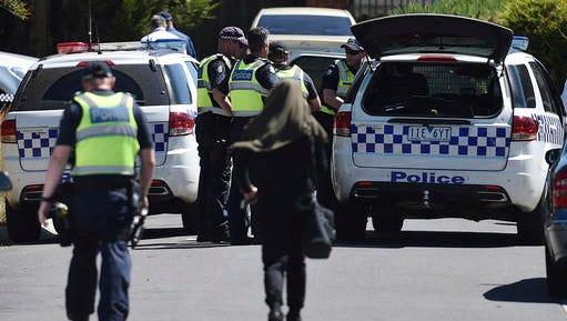 Police accompany a woman as they attend the scene where a house was raided at Meadow Heights in Melbourne, Australia, Friday, Dec. 23, 2016. Police in Australia detained five suspects who were allegedly planning a series of Christmas Day bomb attacks in the heart of the country's second largest city, officials said Friday.