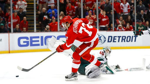 Detroit Red Wings center Andreas Athanasiou (72) scores on Minnesota Wild goalie Devan Dubnyk (40) in overtime during an NHL hockey game Sunday, March 26, 2017, in Detroit. Detroit won 3-2.