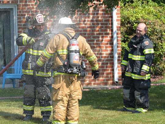 Firefighters hose off turnout gear after battling a
