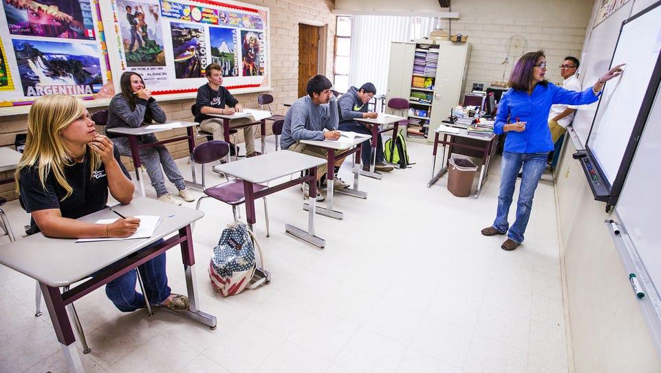 Kelly Coyne, 16, left, listens to her Spanish teacher,