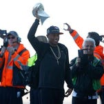 Denver Broncos cornerback Chris Harris, center, holds up the Vince Lombardi Trophy as ramp attendants cheer as players step off the airplane after returning as victors over the Carolina Panthers in Super Bowl 50, Monday, Feb. 8, 2016, in Denver. (AP Photo/David Zalubowski)