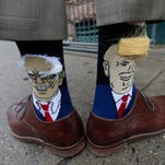 Colorado Gov. John Hickenlooper shows off one of his socks--with Democratic presidential candidate Bernie Sanders while the other bears the likeness of Republican candidate Donald Trump--before entering his former brewpub for a book signing event to mark the release of his autobiography Thursday, May 26, 2016, in Denver. Hickenlooper, who is term-limited, is doing book talk rounds this week, reviving speculation that he is positioning himself to join Hillary Clinton's presidential campaign ticket. (AP Photo/David Zalubowski)