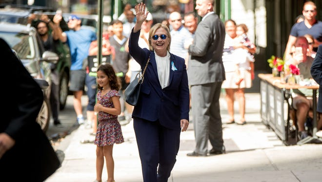 Hillary Clinton waves after leaving her daughter's apartment building on Sunday in New York.