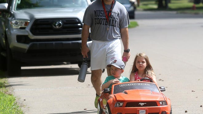 Leah Pellegrino drives her brother Beau to the playground at Dover East Elementary with dad trailing Monday.