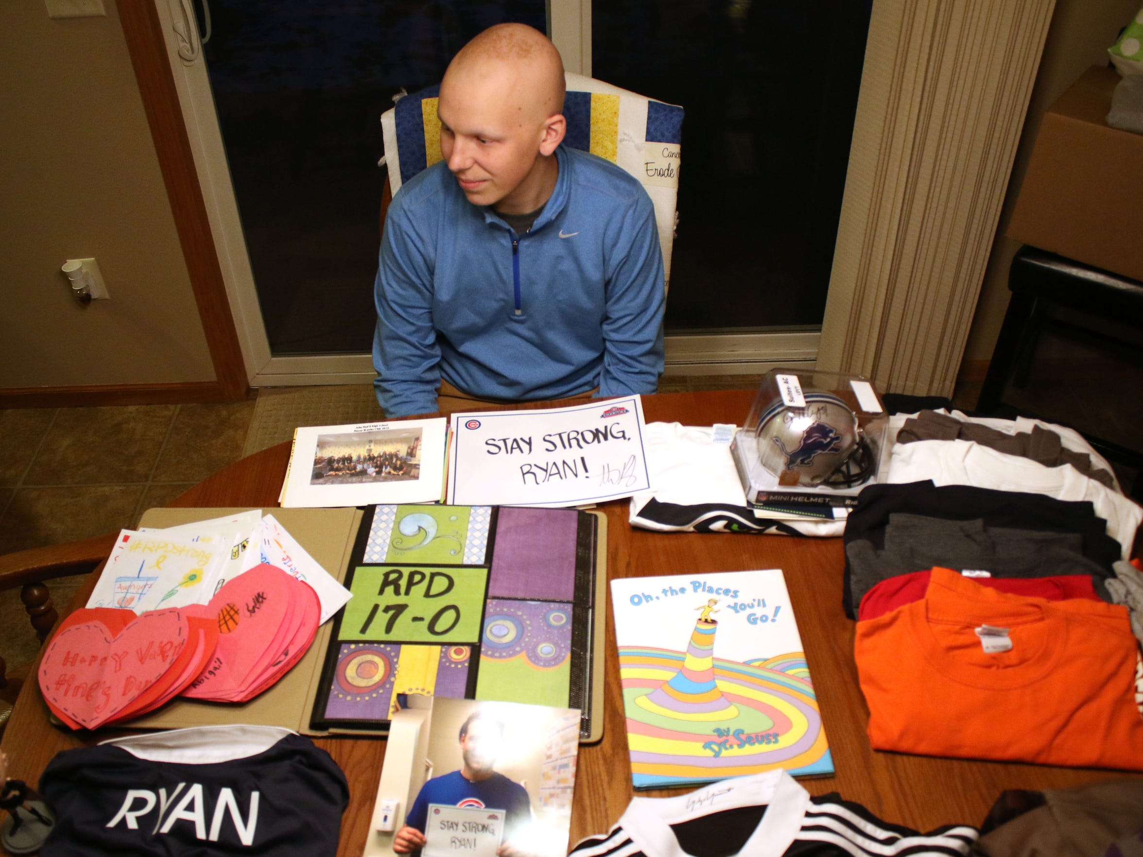 "Ryan Dieringer sits at his kitchen table with a small fraction of the gifts given to him during his 11-month experience with cancer. In late February he was declared to have ""no evidence of disease."""
