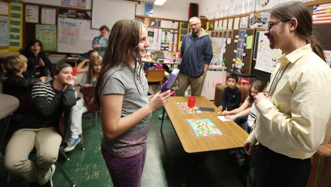 """Book Bin East manager Paul Boers presents fifth-grader Anjolie Palmer with a personally signed version of """"Crenshaw"""" by Katherine Applegate, her favorite author, during class Wednesday, Dec. 16, 2015, at EAGLE Charter School in Salem, Ore."""