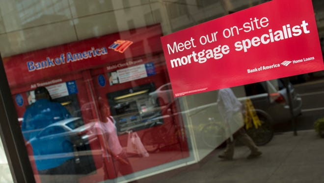 A man uses an ATM as a sticker advertises mortgages at a Bank of America in Washington, DC.