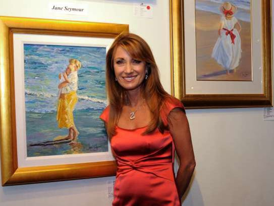 Jane Seymour standing in front of two of her paintings