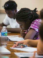 Destiny Cheeks, 15, studies in class.