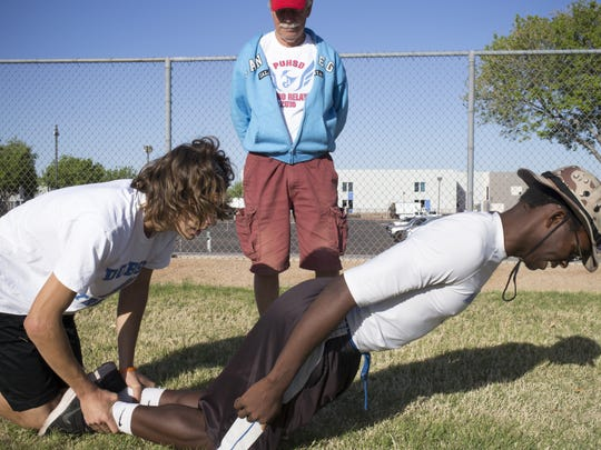 Kyle Brost (left) and Juba McClay stretch on March 15, 2016 before track practice at Dobson High School.