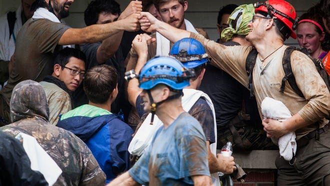 People who were rescued from Hidden River Cave celebrate at a house next to the cave Thursday, May 26, 2016, in Horse Cave, Ky. A group trapped by flash flooding on a field trip to the Kentucky cave Thursday walked through neck-deep water to get to safety, authorities said. (Austin Anthony/Daily News via AP) MANDATORY CREDIT