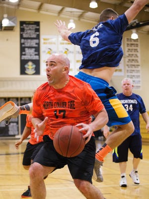Michael Jimenez, of the North Collier Fire Department, competes Sunday in the Heroes in the Community basketball tournament at Bishop Verot High School in Fort Myers.