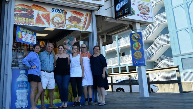 Janet Yilmaz, Adil Yilmaz, Yagmur Karaman, Yesmin Karaman, Ali Karaman and Yasemin Karaman stand in front of their Ocean City boardwalk stand, Golden Plate.  Adil Yilmaz opened the eatery in 1970.