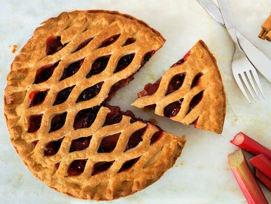 Strawberry and rhubarb pie with slice on marble background