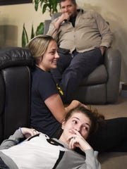 Megan Wyatt, 17, takes a break after decorating the family Christmas tree with her foster sister, Mariah, 18, and her father, Zack, November 30, 2017.