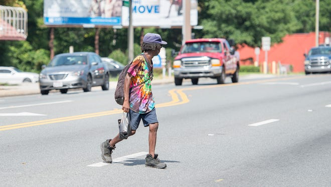 Dwight Colston crosses Cervantes Street between E and F streets in Pensacola on Thursday, June 21, 2018.