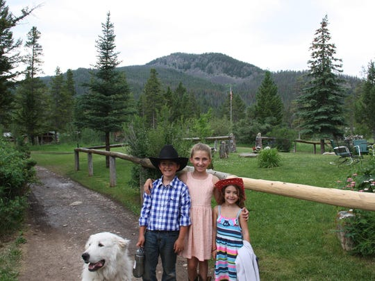 The Wallis' children play on the ranch with their faithful companion.