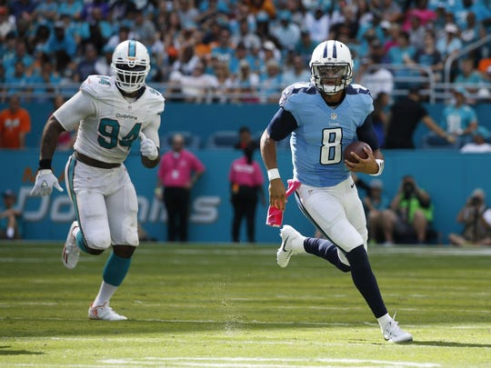 Tennessee Titans quarterback Marcus Mariota (8) runs with the ball ahead of Miami Dolphins defensive end Mario Williams (94), during the second half of an NFL football game, Sunday, Oct. 9, 2016, in Miami Gardens, Fla. Mariota threw for three touchdowns and ran for another. The Titans defeated the Dolphins 30-17. (AP Photo/Joel Auerbach)