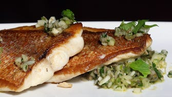Coal-fired fish of the day with caper-fennel relish and charred lemon at Nicky's Coal Fired.