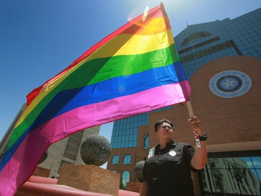 Outright coordinator Becky Silva carried a rainbow flag as she and others celebrated the U.S. Supreme Court's decision on same-sex marriage Friday in front of the El Paso County Courthouse.