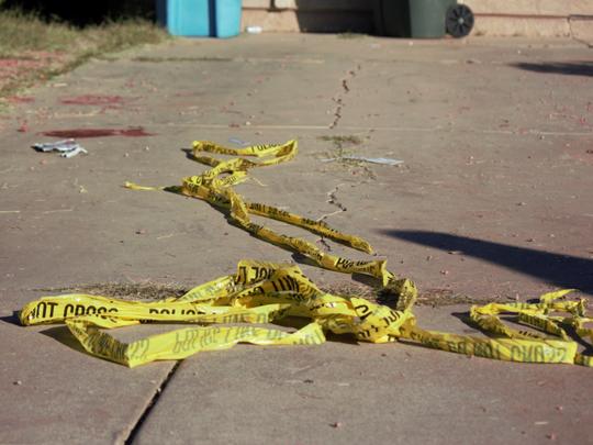 Crime-scene tape and broken bottles remain at the scene